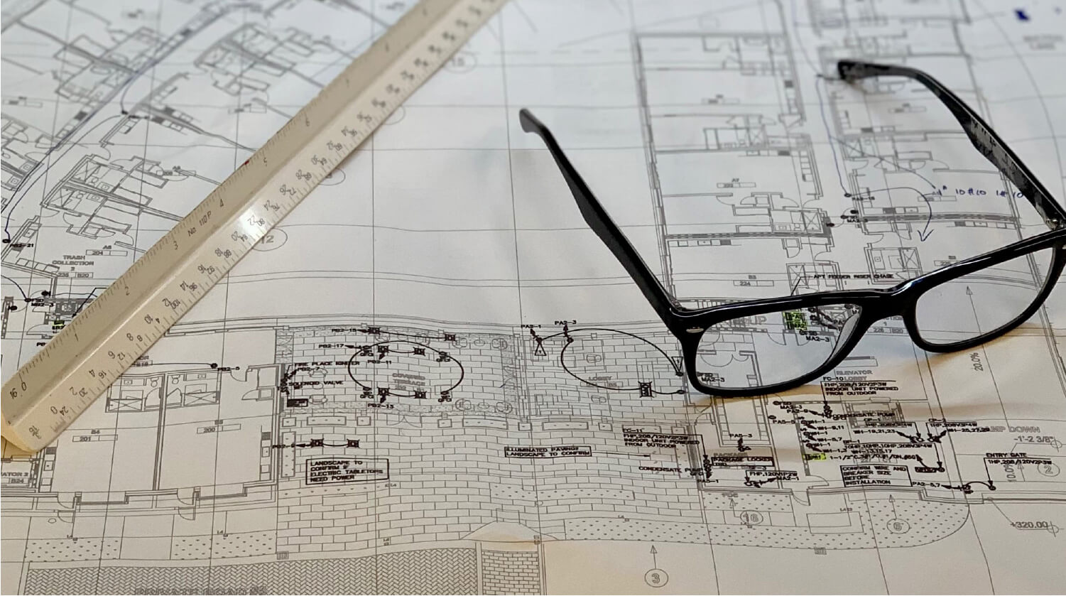 glasses on top of blueprints